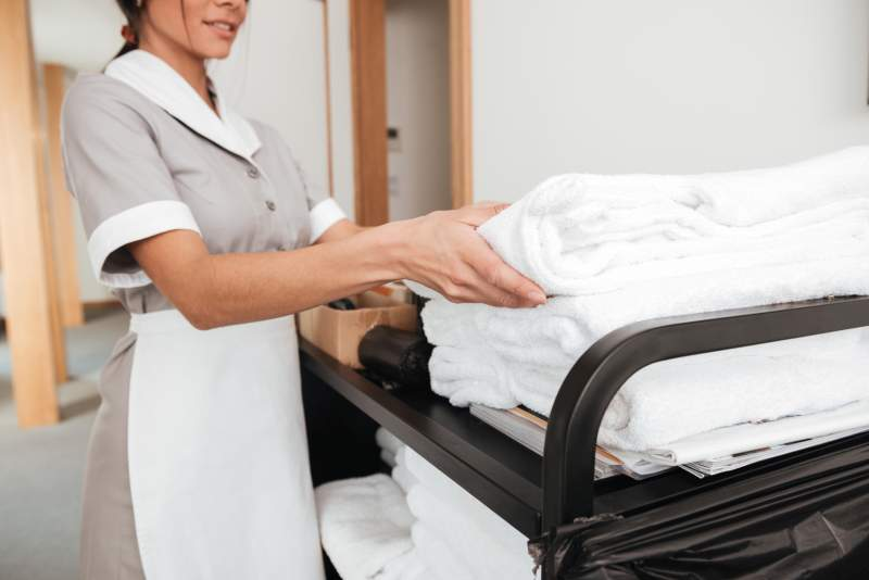 Cropped image of a smiling young maid taking fresh towels from a housekeeping cart